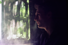 bokeh film photograph portrait young man smoke vape mysterious profile window