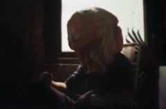 film photograph portrait bokeh surrealist basement window lawn chair seated dark shadowy mysterious person man sitting giant mask head creepy