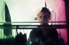 bokeh film photograph portrait young man clothing rack