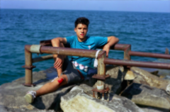 film photography bokeh focus portrait young man sitting beach metal pipes rocks skinned knee bloody