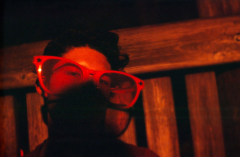 film photography portrait nighttime dark red tint young man party sunglasses giant oversize