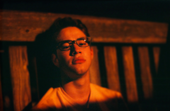 film photography portrait nighttime dark red tint young man