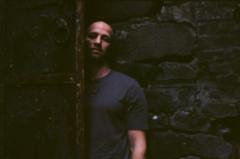 film photography portrait chiaroscuro shadows young man face half hidden stone wall