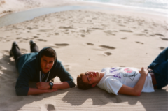 film photography portrait summer two young men lying sand pattern