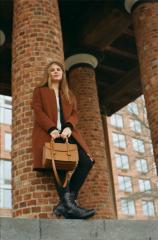 film photograph portrait young woman long hair blonde bokeh brick pillar standing handbag purse