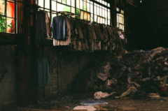 film photography urbex abandoned ruinporn crumbling debris gary indiana screw bolt factory clothing rotting hanging hangers shirts