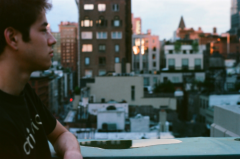 film photograph portrait young man hapa rooftop water puddle reflection city cityscape