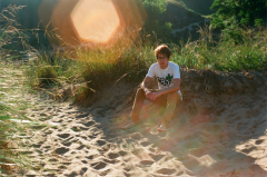 film photography portrait dunes beach sand sitting grass sunspot young man hapa boy