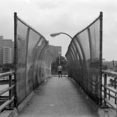 black white photograph film bridge fence chain link young man boy standing perspective
