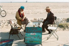 film photograph portrait beach two men hippies chess game donate or kiss the pigs brass ass
