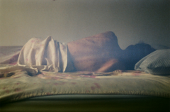 film photograph bed person lying sheets nude gua sha back marks scary