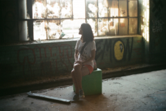 film photograph young woman girl sitting abandoned building broken window urbex exploring