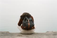 film photograph portrait woman sitting back turned edge of water backpack knapsack