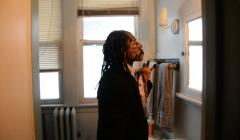 portrait african american man standing in front of the bathroom mirror dreadlocks suit face paint charcoal no slaves adjusting tie