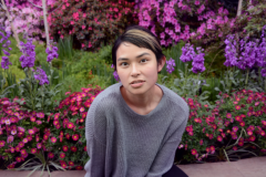 digital photograph portrait model plants conservatory hothouse leaves girl young woman sitting asian sweater short hair pixie cut fashion flowers pink red