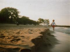 film photograph beach soft lighting little girl running sand cliffs sculpted natural