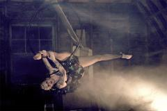 a girl posing on an aerial hoop ring lyra circus splits  pose black dress blonde tattoos misty mysterious magic magical