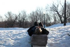 a woman lying on her back on a concrete block in the snow napping siesta