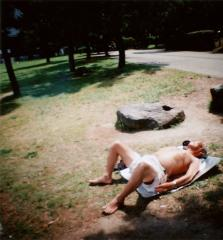 film photograph of a man taking a nap old ojisan sunbathing asian blanket park grass lawn green