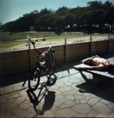 film photograph of a man taking a nap summer sunbathing stretch sprawled out bike