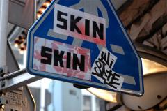 photograph of graffiti on a street sign covering skin spraypaint strange