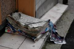 Photograph of an old telephone book sitting on a doorstep wet dirty waterlogged crumpled trash found art still life torn